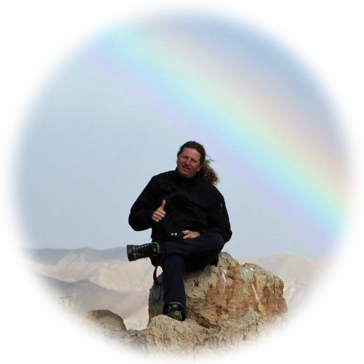 Ori sits on a rock with a rainbow behind